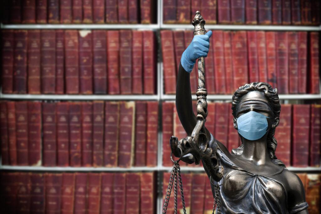 Justizia mit Corona-Maske vor Bücherregal