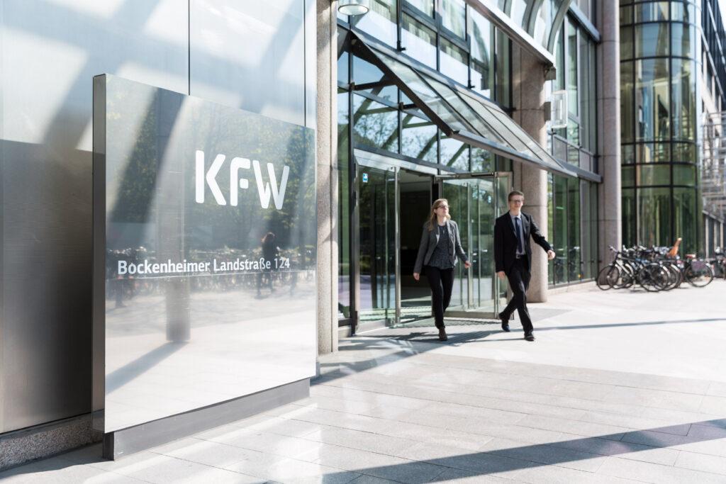 Zwei Mitarbeiter kommen aus dem Eingang der Nordarkade der KfW Zentrale in Frankfurt.
