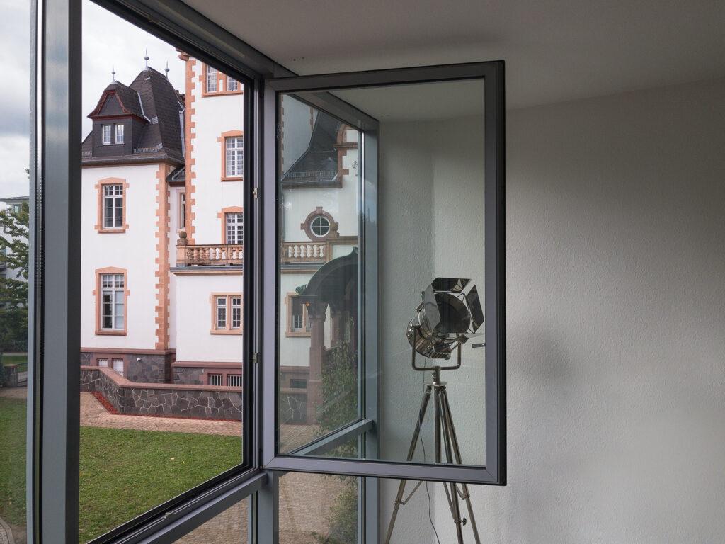 Offenes Fenster zur Belüftung des Besprechungsraums mit Blick auf die Villa.
