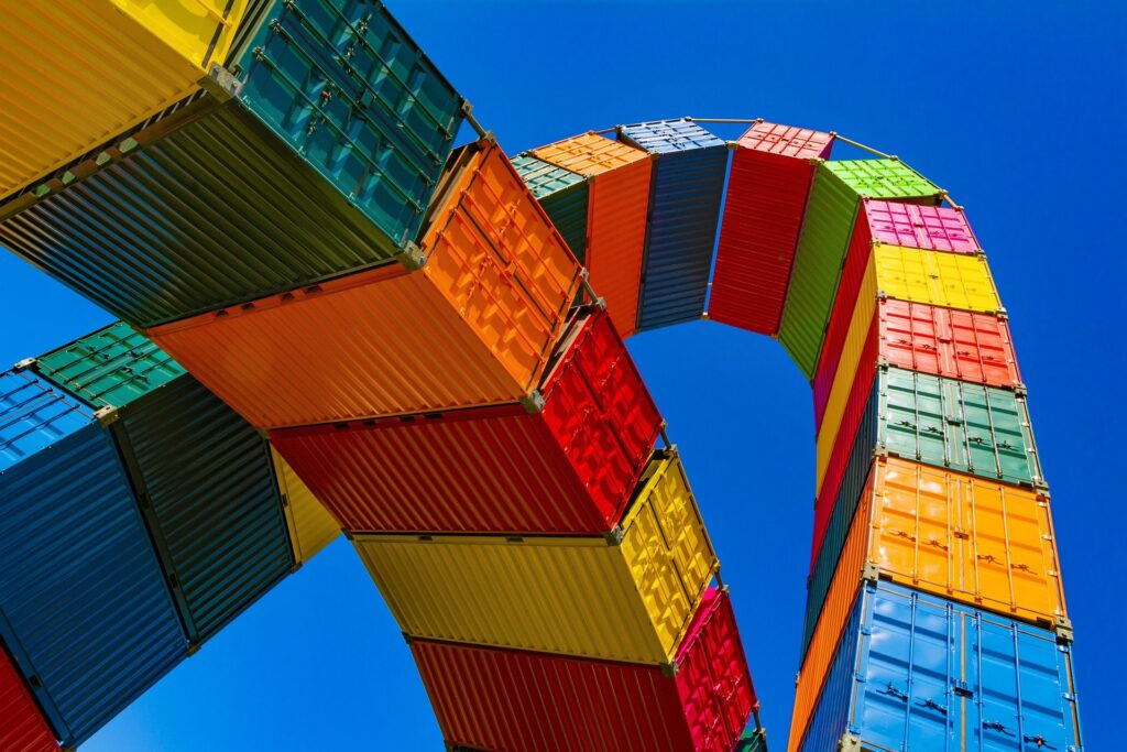 Bunte Container, zu zwei Bögen verbunden, in den Himmel ragend