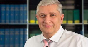 Portrait von Oliver Wendland, Rechtsanwalt, vor einem Bücherregal