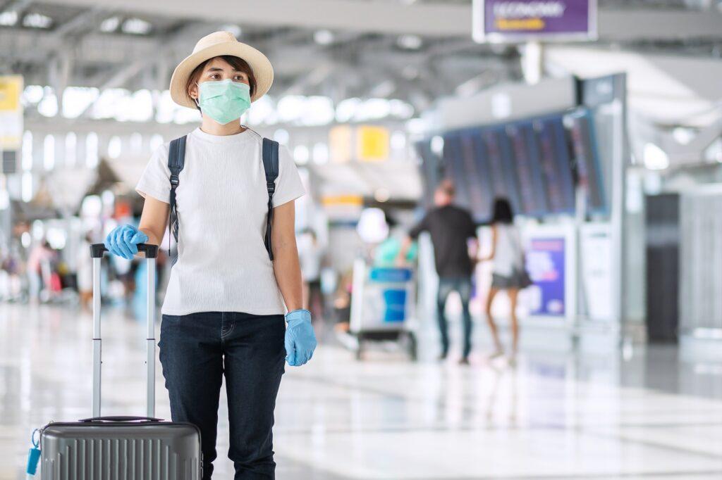Reisende am Flughafen mit Mund-Nasen-Maske und Handgepäck.