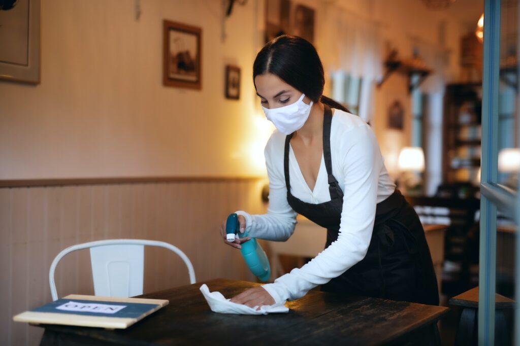 Junge Frau mit Gesichtsmaske desinfiziert einen Tisch in der Gastronomie