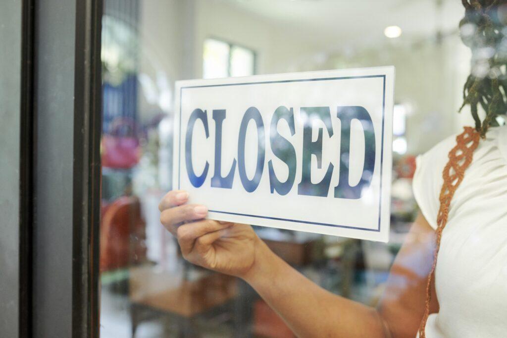 Wegen Corona geschlossenes Ladengeschäft mit Schild im Schaufenster