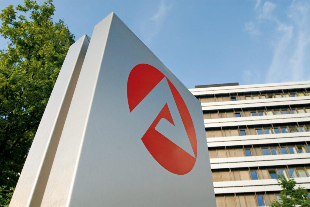 Zentrale der Bundesagentur für Arbeit in Nürnberg mit Logo im Vordergrund