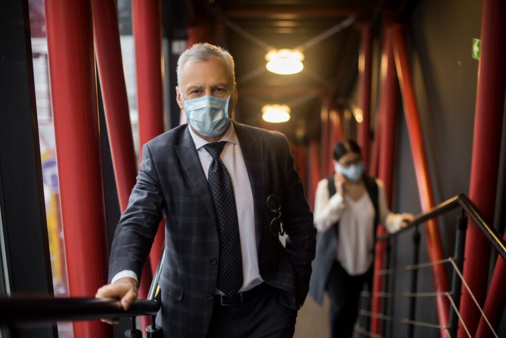 Geschäftsmann im Anzug geht mit medizinischer Corona-Schutzmaske eine Treppe hinauf.