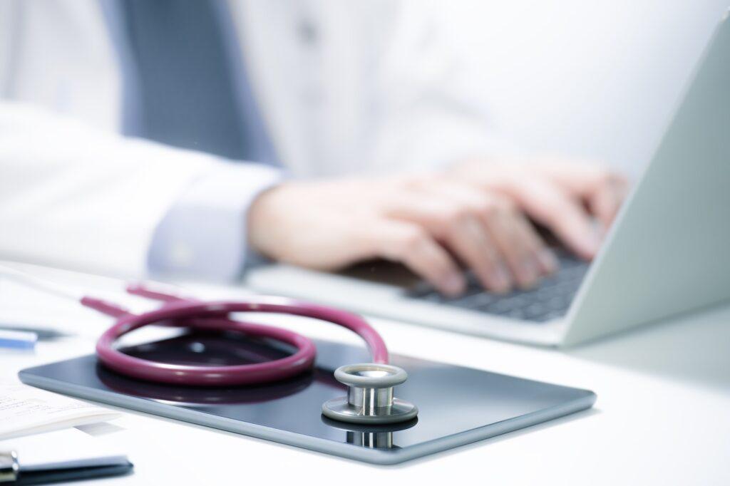 Arzt gibt Daten in seinen Laptop ein.