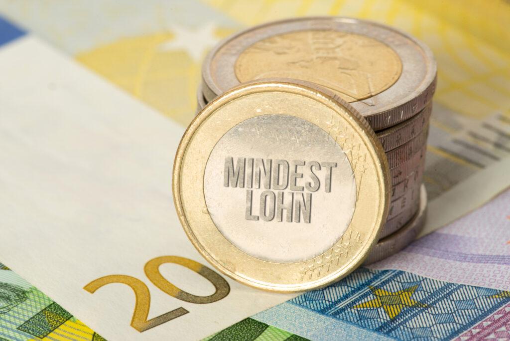 Mindestlohn symbolisiert durch einen Stapel Münzen auf einem 20-Euro-Schein