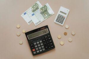 Taschenrechner, Geldscheine und Münzen liegen auf einem Tisch