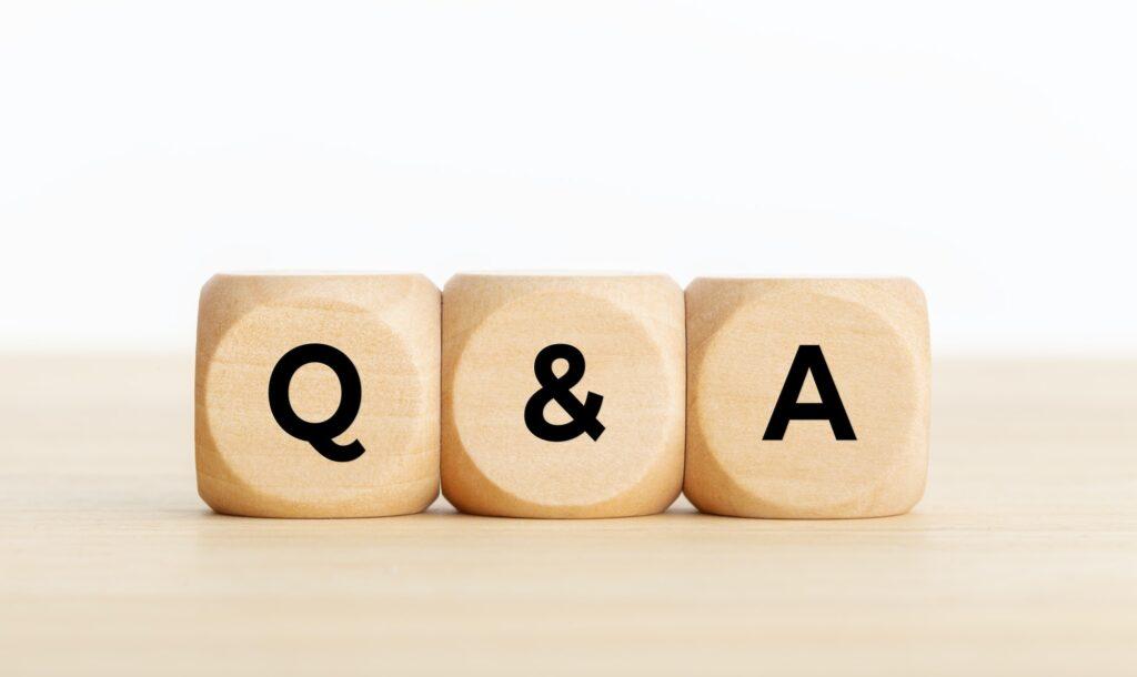 Fragen und Antworten, symolisiert durch die Zeichen Q-&-A auf hellen Holzwürfeln