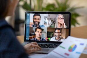 Person sitzt vor dem Laptop und nimmt an einer Videokonferenz teil.