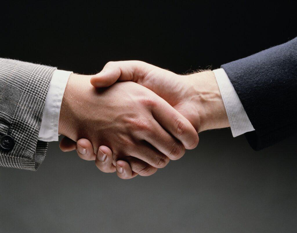 Nahaufnahme zweier Hände von Geschäftsmännern in Anzügen, die sich die Hände schütteln.