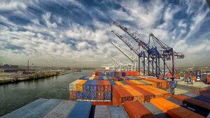 Containerhafen mit bunten Containern und mehreren Verladekränen an einem Fluss.