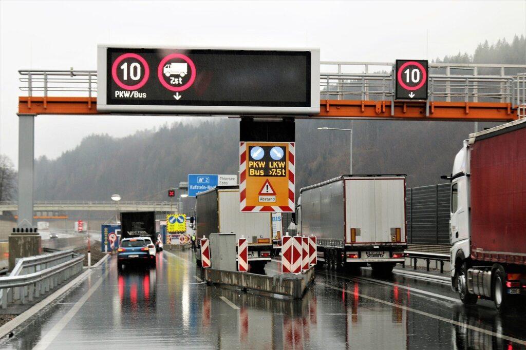 Mehrere Lastwagen werden an der Grenze kontrolliert. Die Straße ist nass. Über der Straße hängen Verkehrsschilder.
