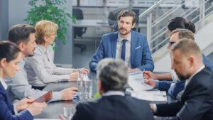 Menschen in einem modernem Konferenzraum führen eine Tarifverhandlung.