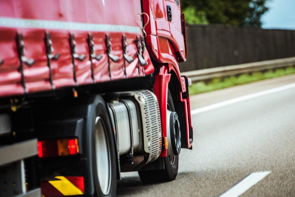 Roter Lastwagen auf einer Straße als Teil der Lieferkette.